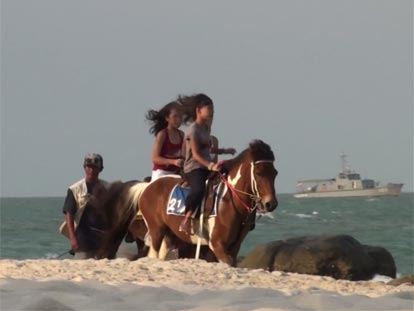 Girls on horseback riding along Hua Hin beach
